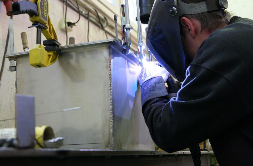 """Locket till St. Olav Hospitals tidskapsel svetsas fast för att skapa en hermetiskt sluten miljö inne i kapseln. Den goda stålkvaliteten och kapselns lockkonstruktion som gör det möjligt att svetsa i en utskjutande """"läpp"""" minskar risken för skadlig värmepåverkan på kapselns innehåll. Foto: Dag Øivind Antonsen (CC BY-SA 4.0)"""
