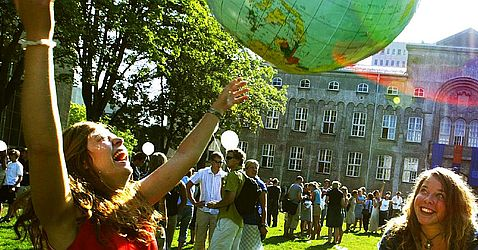 Students playing with huge ball that looks like planet earth after the immatrikulation ceremony. Photo.