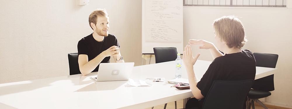 To menn som sitter i møte.