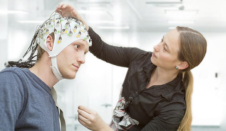 Dame tar på hette med elektroder på mann