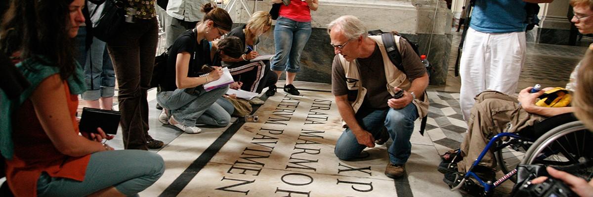 Studenter og ansatte ved Fakultet for arkitetktur og design studerer skrift på gulv i Roma.