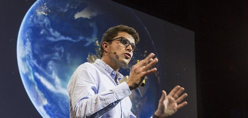Mann holder presentasjon foran en skjerm med en jordklode på. Foto.