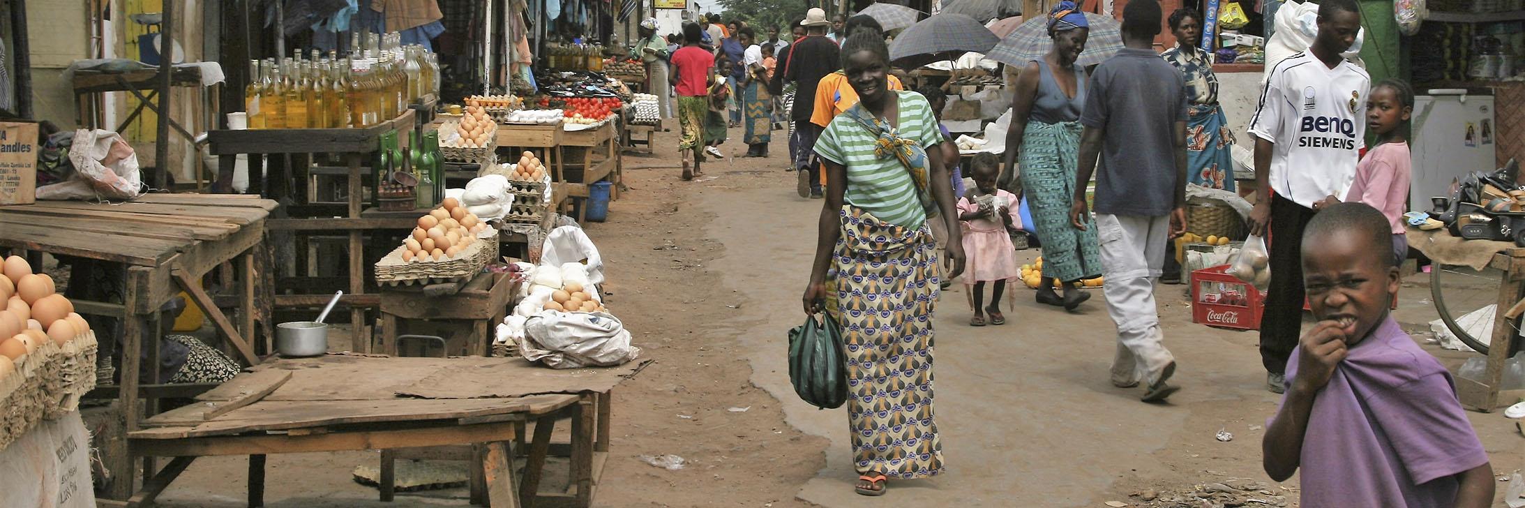 Dame går gjennom et marked. Foto.