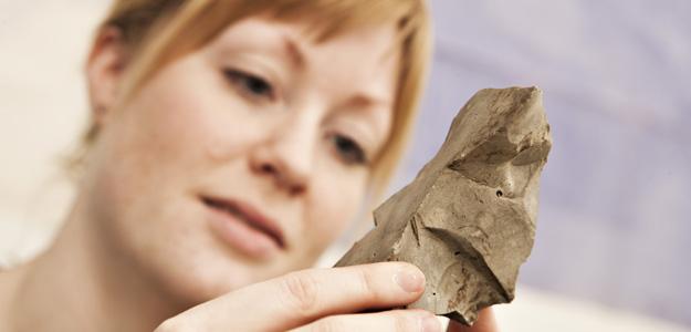 Bilde av kvinne som holder en steinaldergjenstand