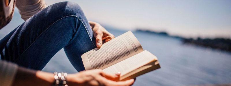 Student som leser bok ved sjøen