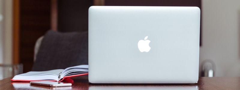 Bilde av en Mac og en oppslått bok