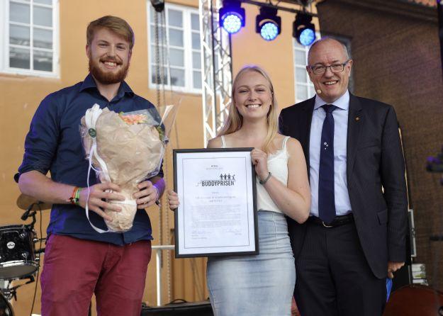 to studenter med blomster og diplom står sammen med rektor Bovim