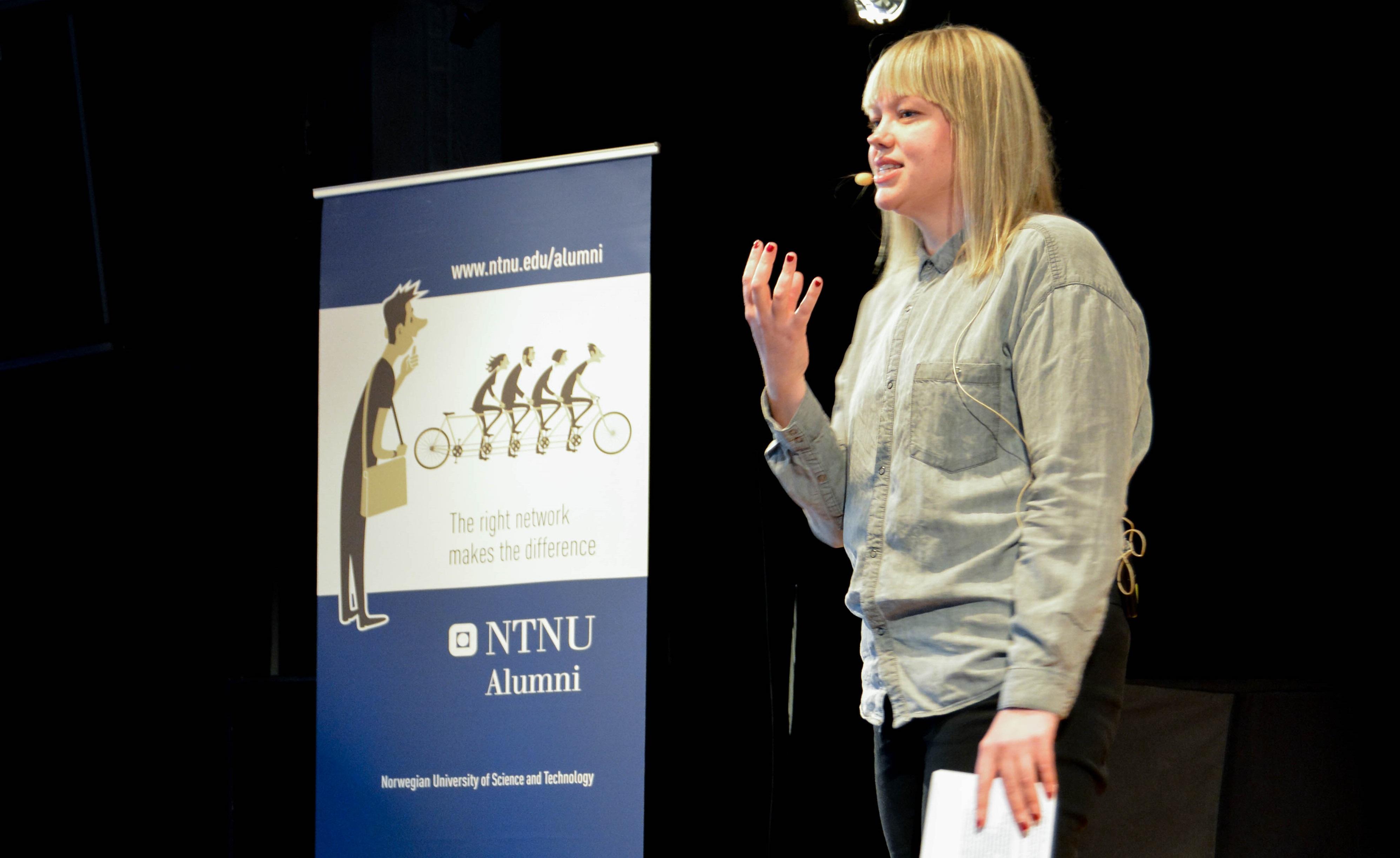 Alumn står på scenen og snakker til studentene. Foto: Stine Krogh Hagen