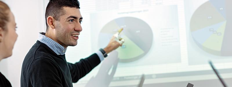 En mann peker på en graf på en tavle