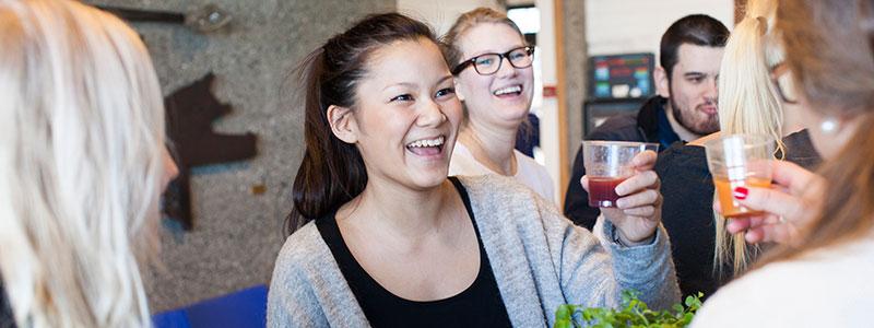 Glade studenter med kopper med drikke. Foto