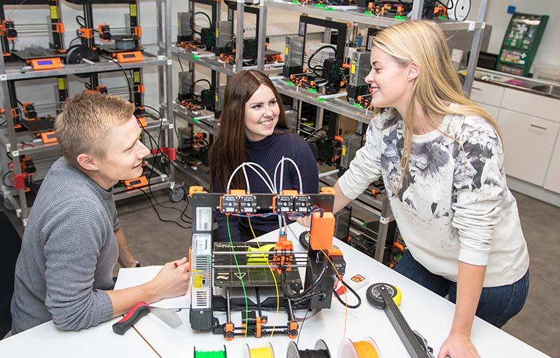 Tre studenter med en mini-3D-printer