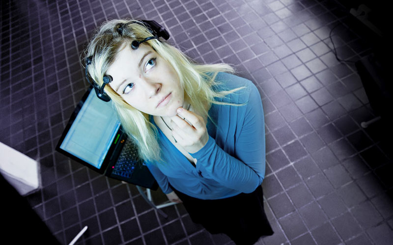 Female student with headphones in front of a laptop. Photo