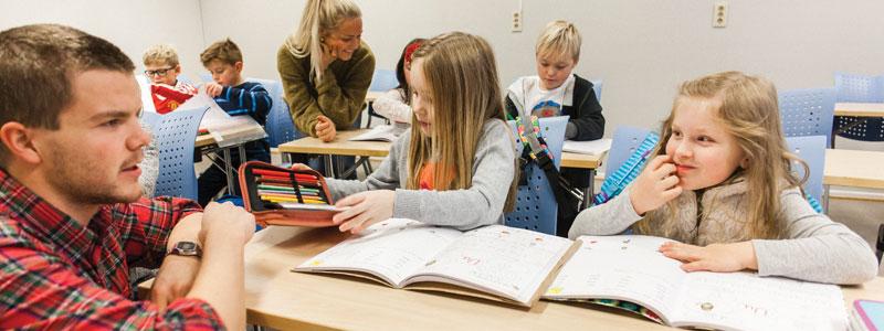 Student hjelper elev med lekser. Foto.