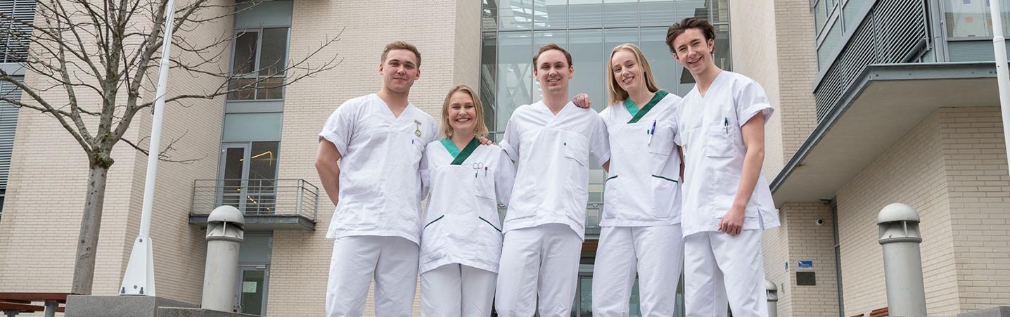 Fem sykepleierstudenter utenfor bygning.