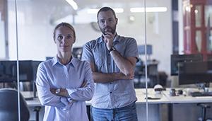 Alvorlig kvinne og mann i kontorlandskap som ser rett mot kameraet. Bilde