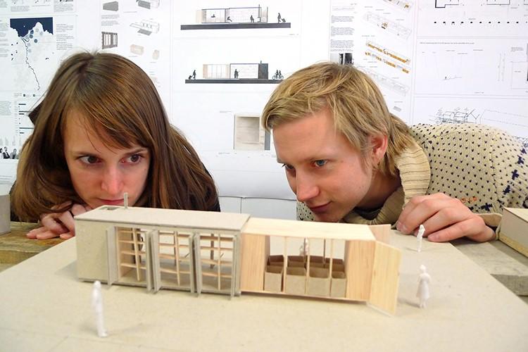 Illustrasjonsbilde med kvinnelig og mannlig arkitektstudent som ser på en miniatyrmodell i tre.
