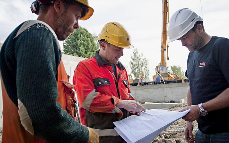 Illustrasjonsfoto av tre menn på byggeplass med hjelm som ser på byggetegninger.