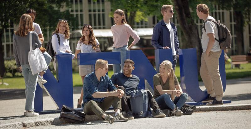 "Studenter i sola som står rundt bokstavene ""NTNU"". Foto."