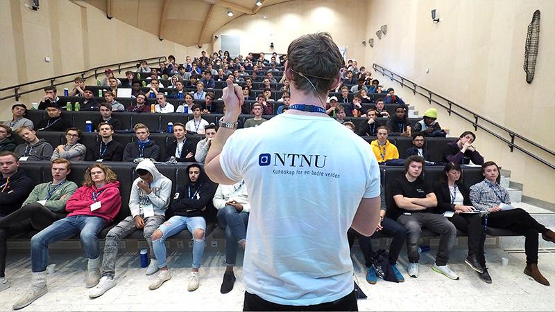 Student med NTNU-skjorte står i et auditorium fullt av gutter. Foto.