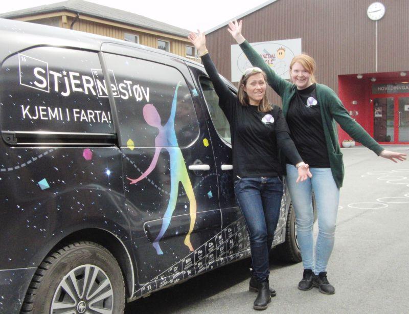 Unni og Ingeborg foran en bil dekorert med periodesystem. Foto