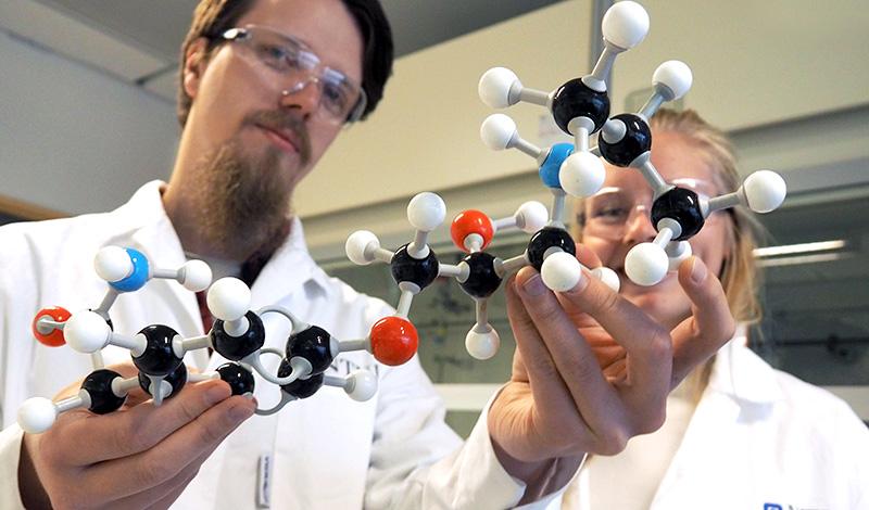 Studenter som viser opp en modell av atomer. Foto