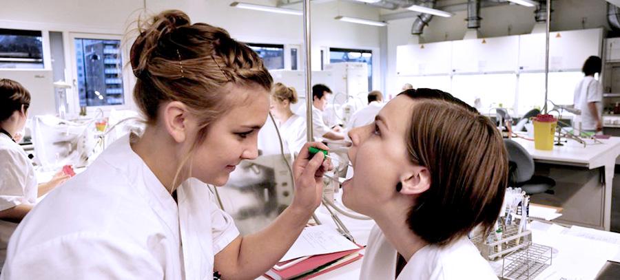 En student tar en munprøve av en annen student på laben. Foto