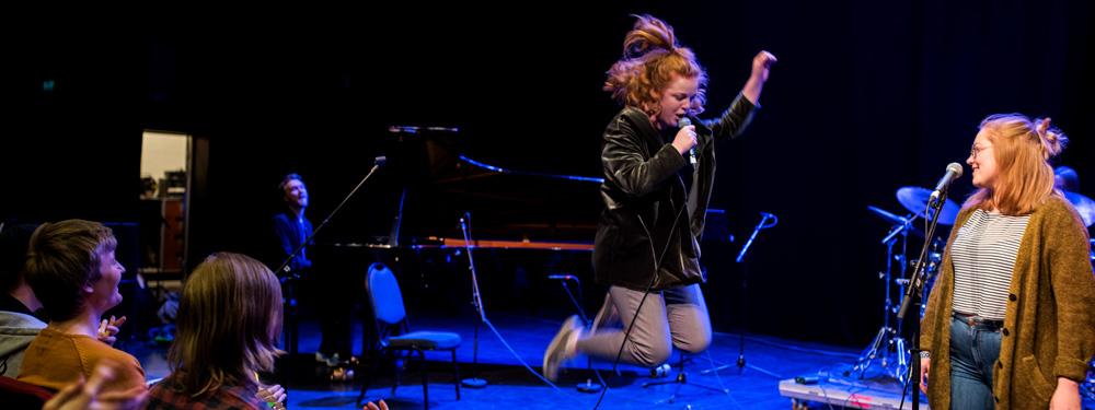 Kvinnelig vokalist som hopper på scenen.
