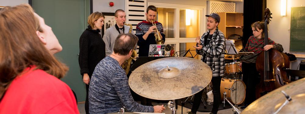Sju musikere spiller sammen i et klasserom