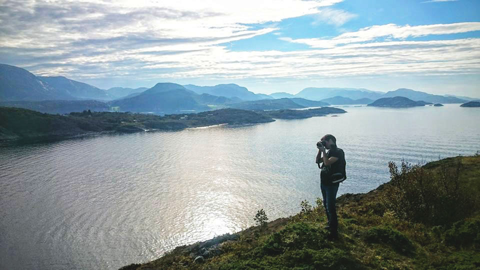 Student taking photo by the the fjord with sunshine and clouds. Photo.