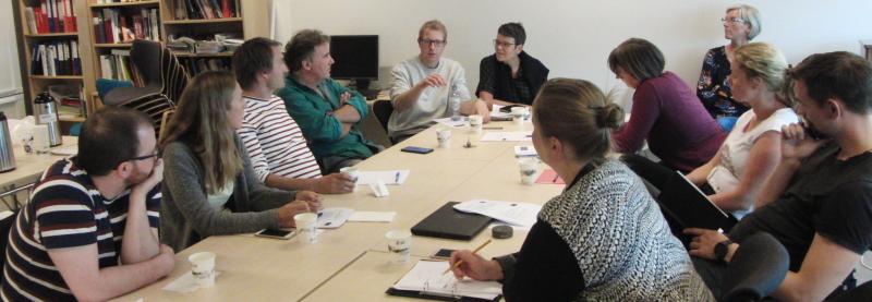 Lærere som sitter rundt et bord og diskuterer. Foto.