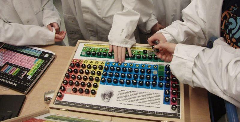 Elever utforsker en koffert med grunnstoffer. Foto.