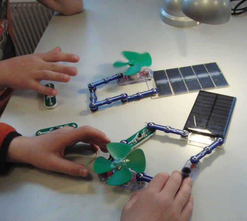 Elever som tester ut solceller og vifter i elektriske kretser. Foto.