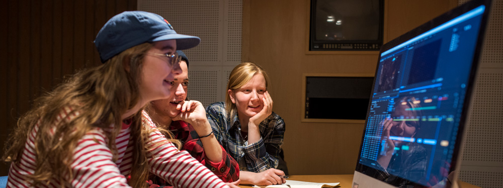 Tre studenter sitter foran data og redigerer fiml