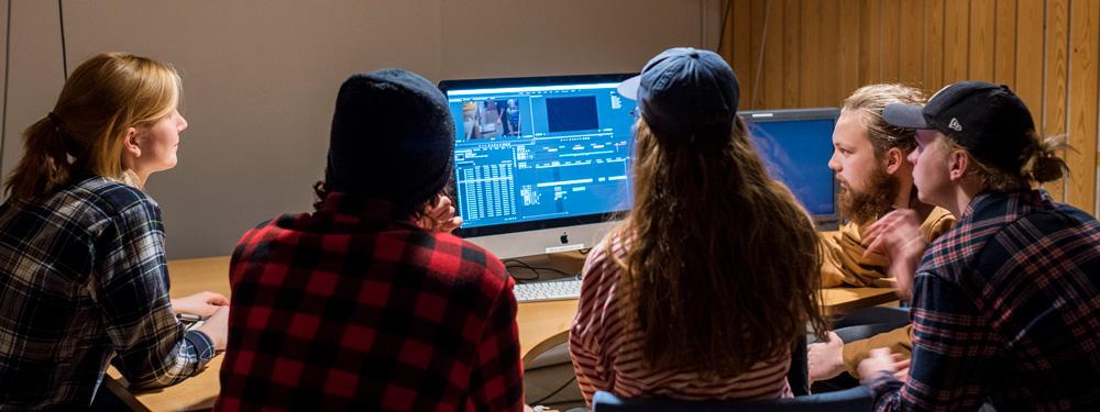 Fem studenter sitter foran datamaskin og redigerer film