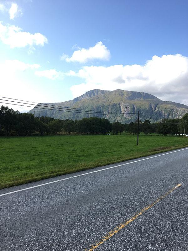 Landskapsbilde som viser en veg og et fjell. Foto.