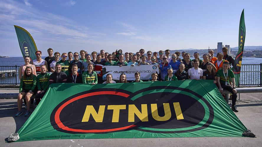 Mange mennesker iført NTNUis grønne, gule og sorte farver sitter ved sjøen med et stort NTNUi_flagg foran seg. Foto.