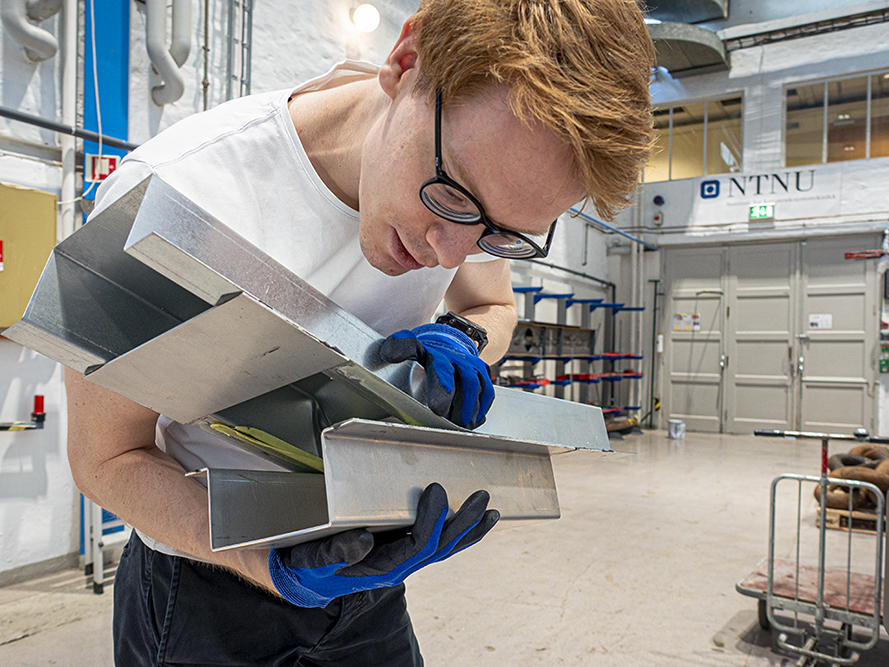 Young man holding bonded components in steel and aluminium