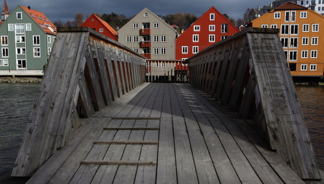 Photo: Bridge and wooden houses by the riverside.